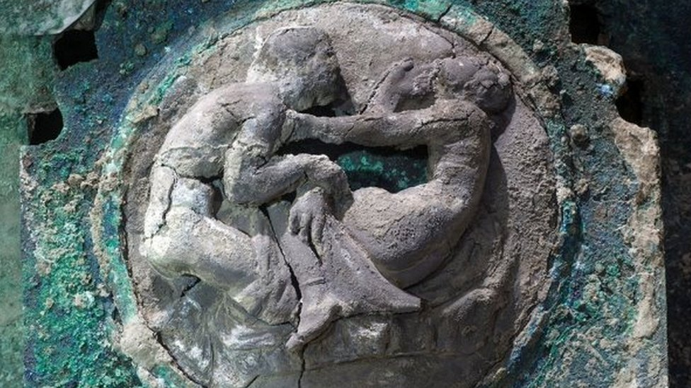 Close-up of design shows two figures