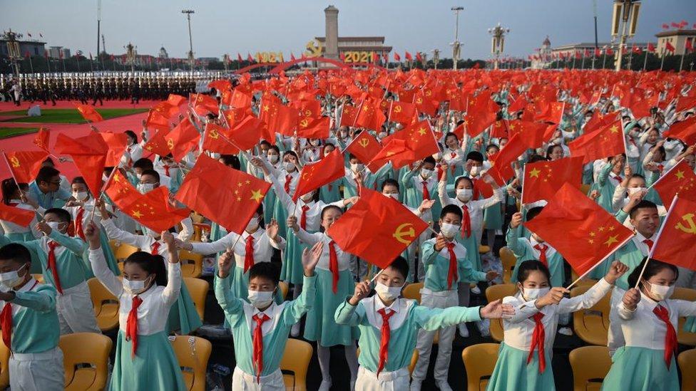 estudiantes ondean banderas de China y del PCCh en Pekín el 1 de julio, en la plaza de Tiananmen.