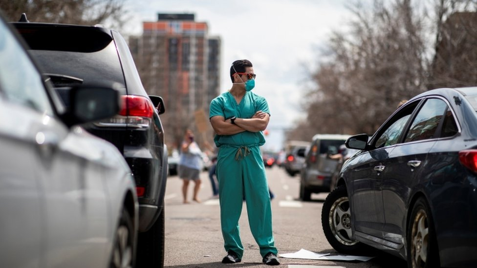Protests against virus shutdowns in Denver on 19, April meet two counter-protesters dressed as healthcare workers