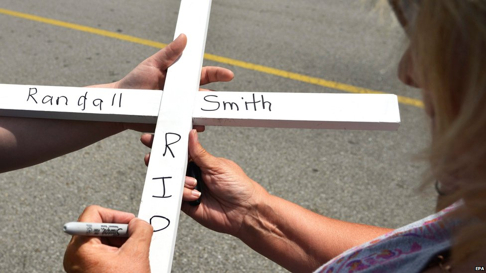 A mourner writes the name of Randall Smith - another victim of the shooting in Chattanooga, Tennessee, shootings, who died of his wounds on Saturday - on a cross
