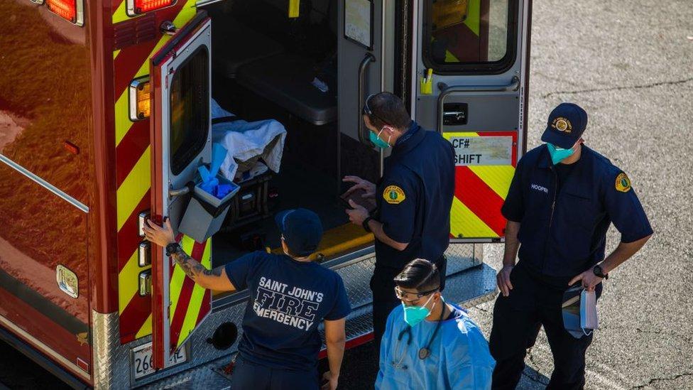 Trabajadores de la salud se preparan para sacar un paciente en camilla de una ambulancia