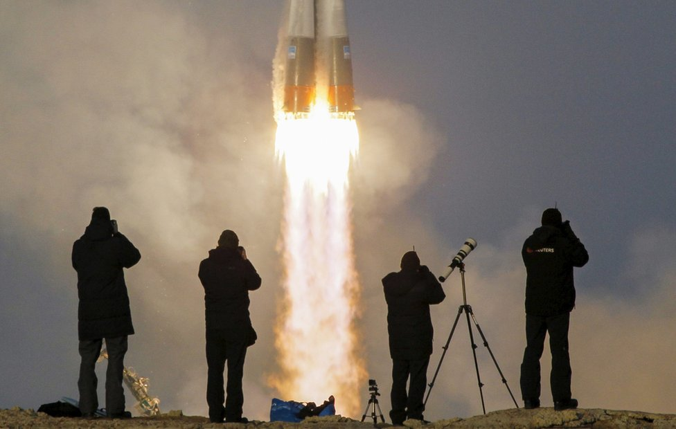 Photographers taking pictures of the Soyuz spacecraft launch
