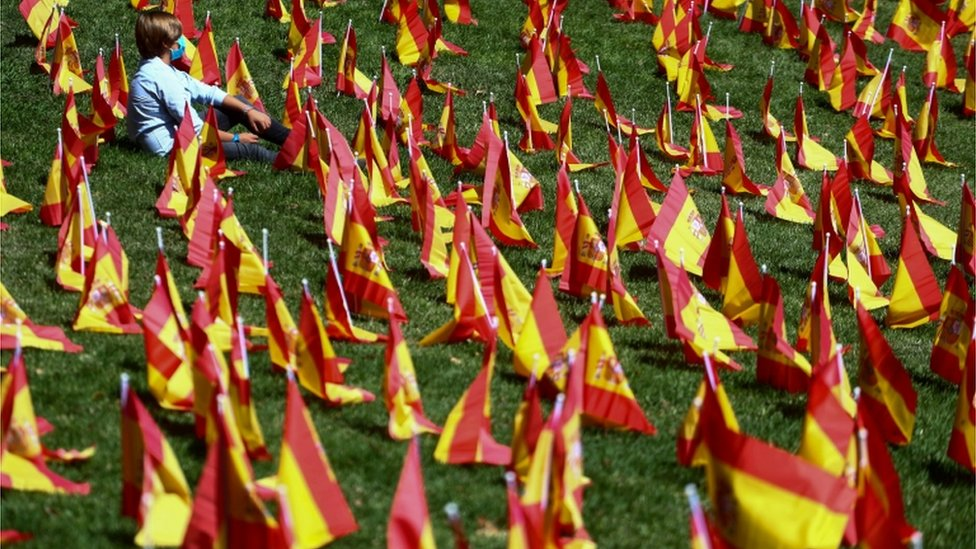 A boy sits among dozens of Spanish flags in Madrid