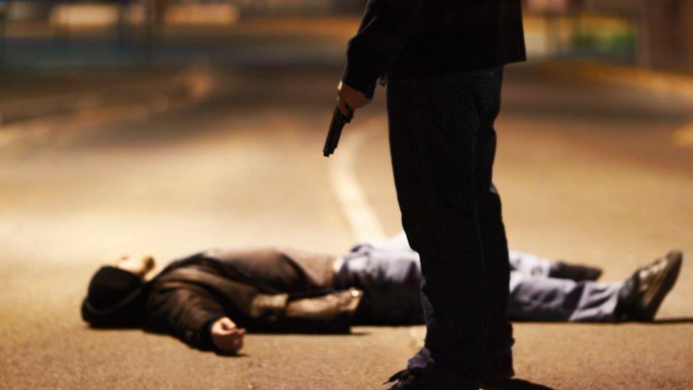 Sicario y un hombre tendido en el suelo