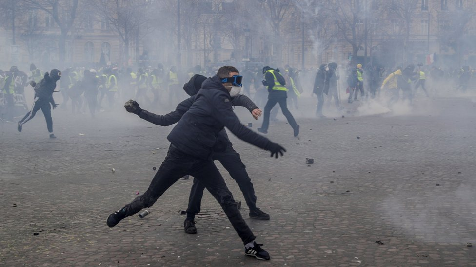 Demonstrators throw cobblestones at riot police forces during clashes near the Arc de Triomphe in Paris on March 16, 2019