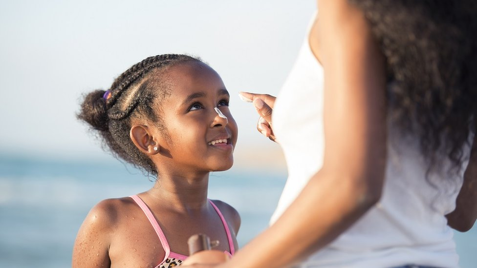 Mother applies sun protection cream to her six-year-old daughter on a beach