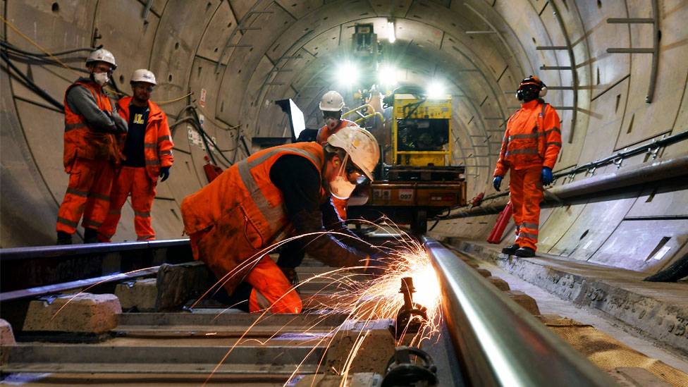 Construction workers work on a section of train track inside a Crossrail tunnel, beneath Stepney in east London in 2016