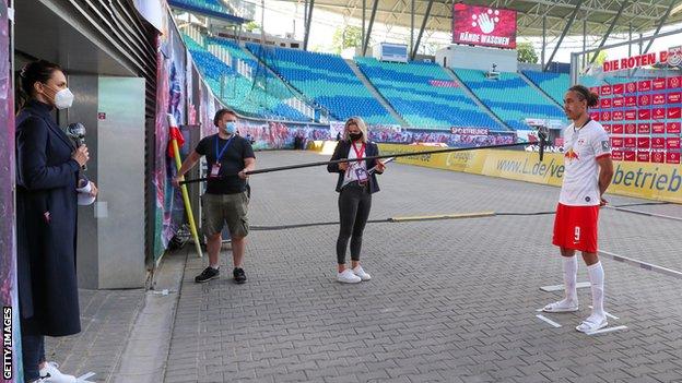 RB Leipzig striker Yussuf Poulsen is interviewed from a safe distance