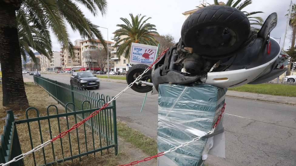 A motorbike is perched atop a plastic-wrapped speed camera in Ajaccio on the French Mediterranean Island of Corsica, on December 2, 2018,