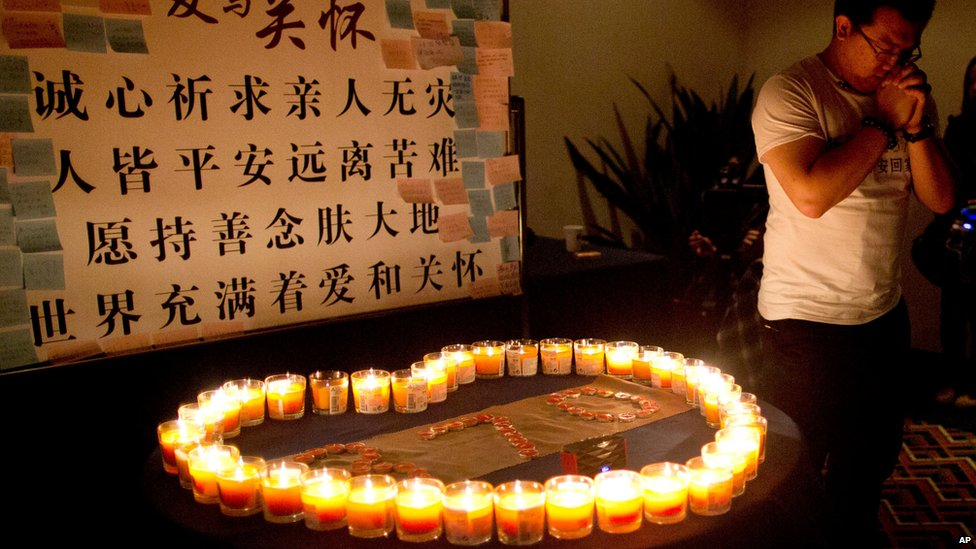 A relative of a Chinese passenger on board MH370 prays near candles before a briefing with Malaysian officials at a hotel in Beijing, China (March 31, 2014)