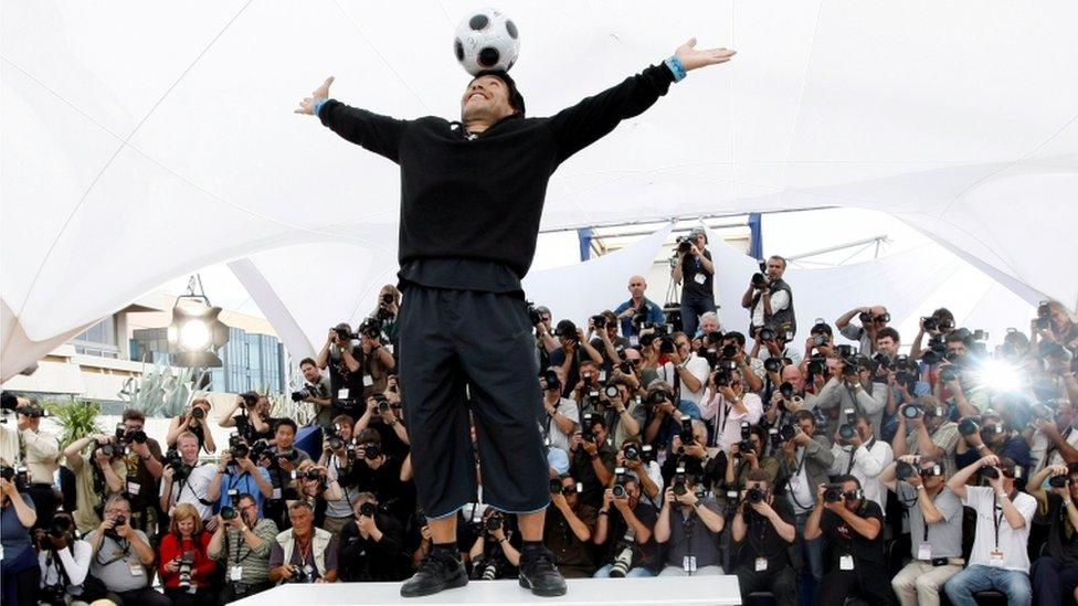 Maradona siendo fotografiado.