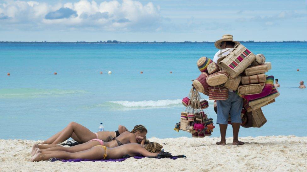 Mujeres tomando sol en la playa mientras un vendedor las mira en México.