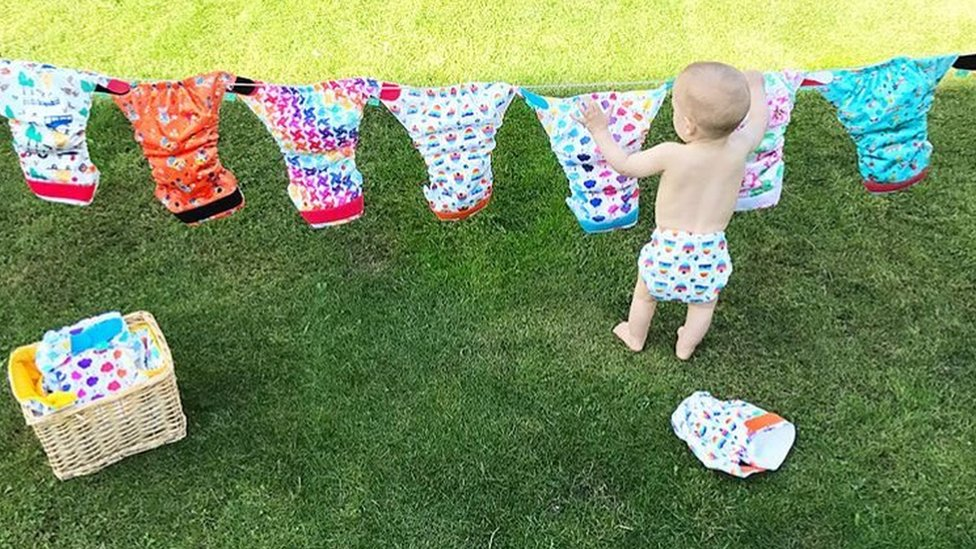 Baby hanging nappies on a clothes line