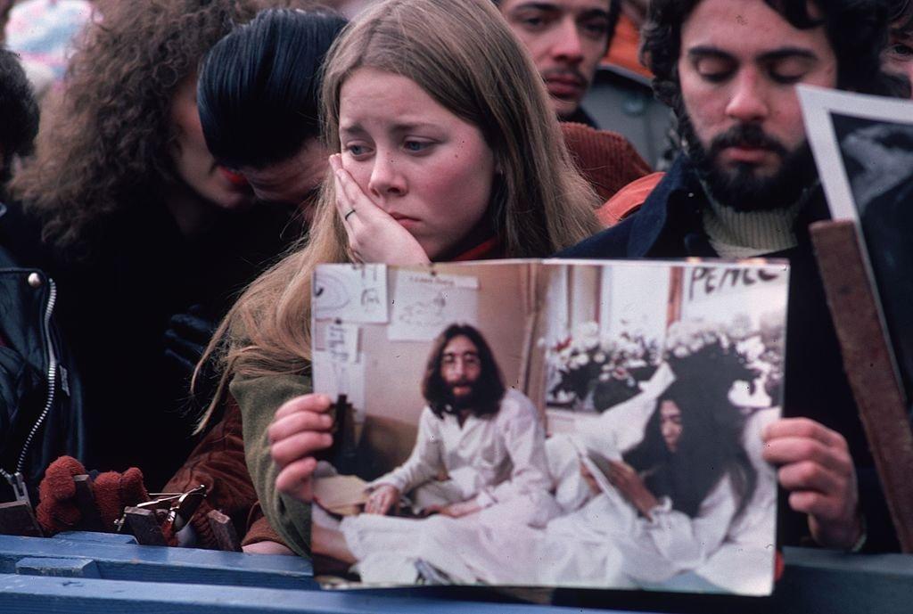 Jóvenes apesumbrados con una foto de John Lennon, lamentando su muerte