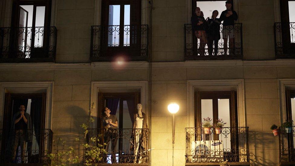 Gente aplaudiendo en los balcones.