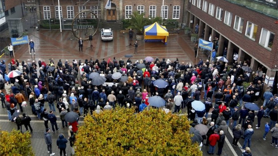 A crowd gathers as Sweden Democrat parliament member Kent Ekeroth speaks during a demonstration to strengthened border controls held at the Radhustorget Square in Trelleborg, Sweden, on 17 October 2015.