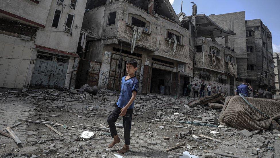 Un niño caminando entre los escombros en Gaza.