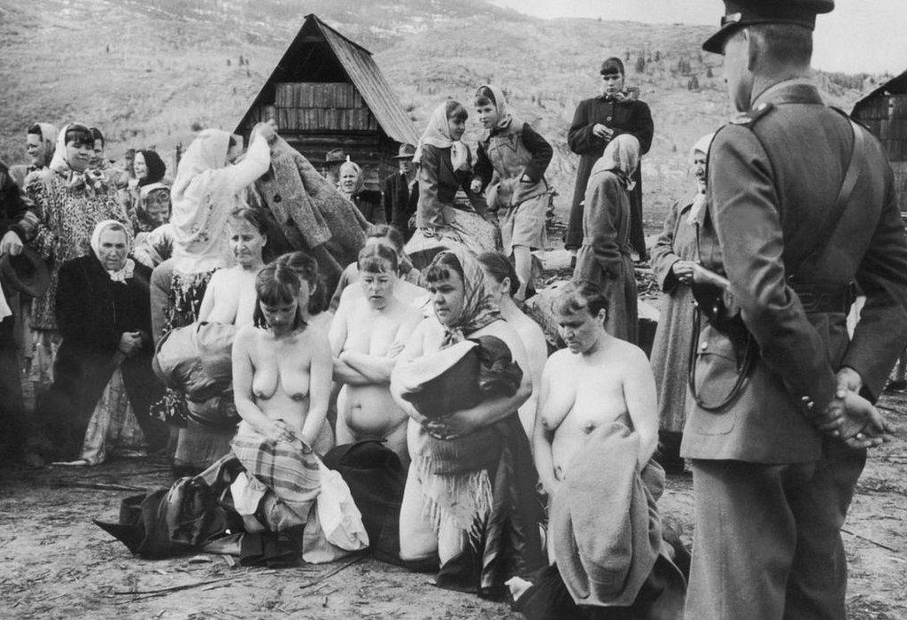 Policía observa mujeres vestidas y desnudas protestando.