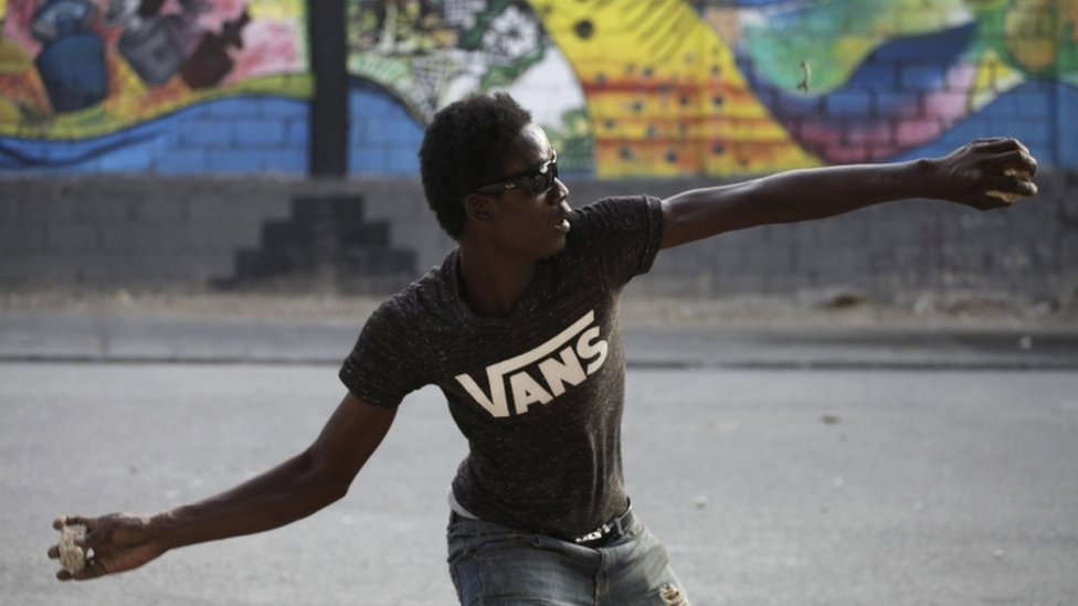Opposition protester hurls a stone in Port au Prince