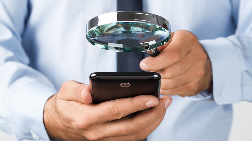 Hombre sosteniendo una lupa sobre un celular.