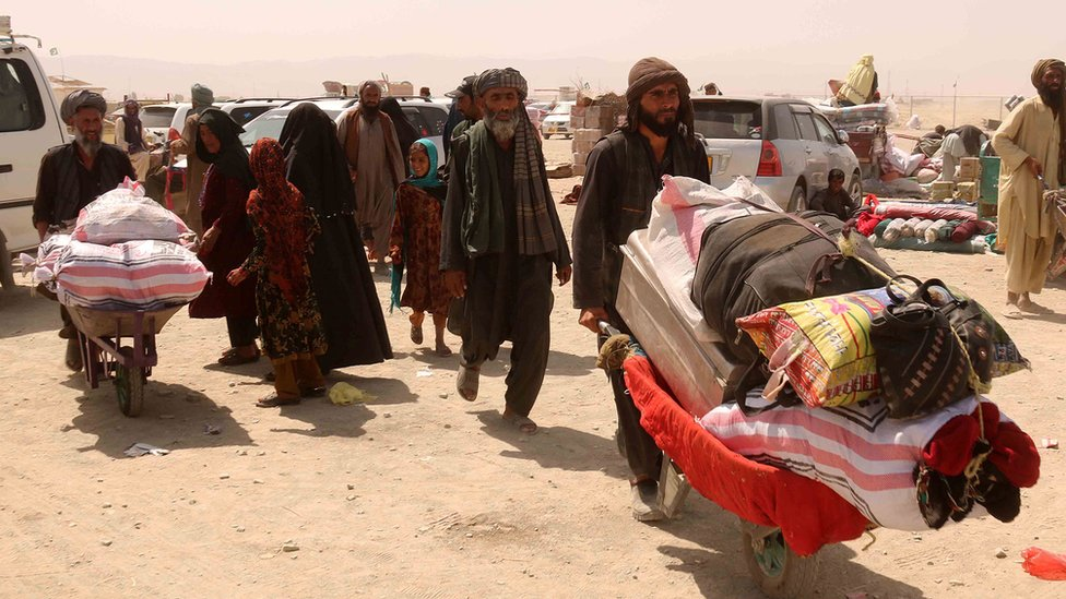 Los afganos transportan sus mercancías en carretillas hasta la frontera