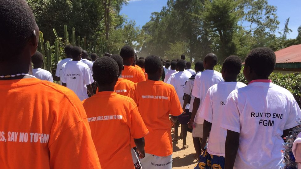 """Students walk in a line wearing orange t-shirts that say """"Protect girls, say no to FGM"""" and white t-shirts saying: Run To end FGM"""