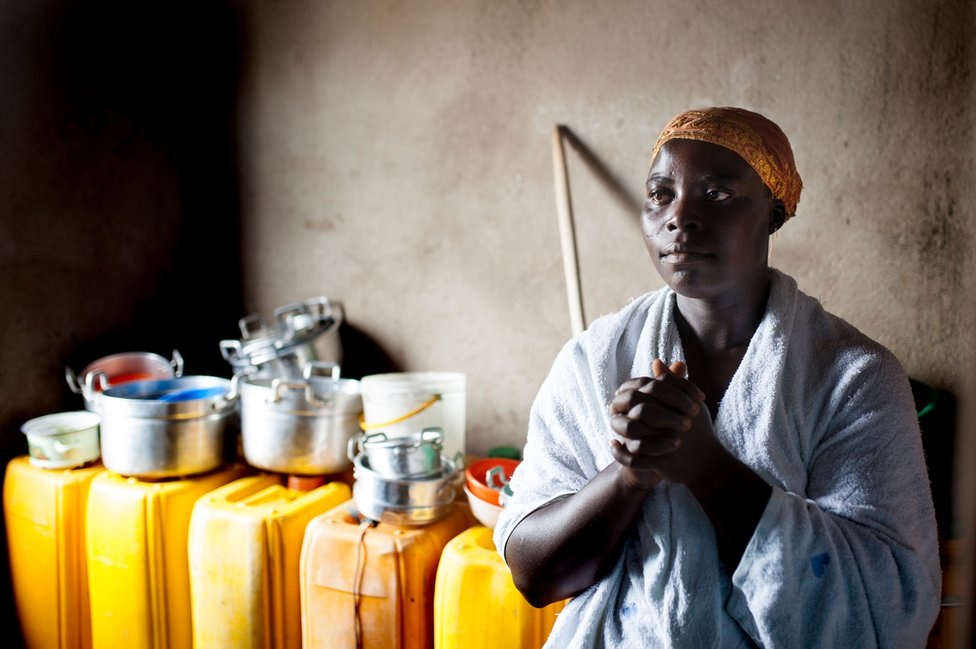 Hannah Abekah prays in front of the yellow buckets of rainwater she has collected