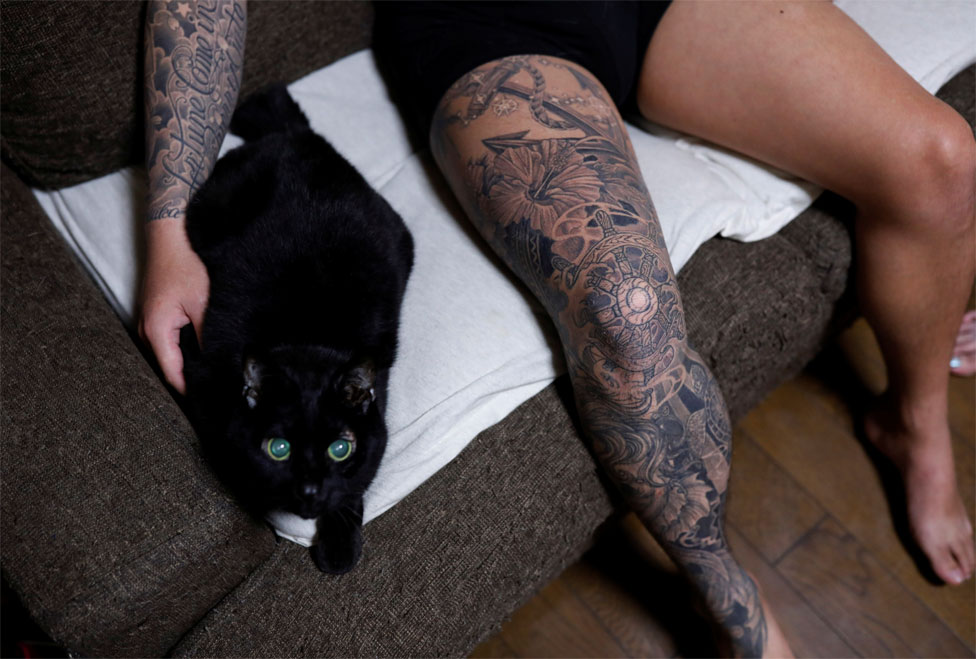 A man with tattoos on his arm and leg pets a black cat on a sofa