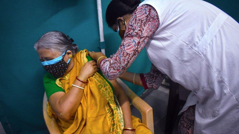 A woman receives a dose of COVISHIELD, a coronavirus disease (COVID-19) vaccine at a Kolkata Municipality medical centre in Kolkata.