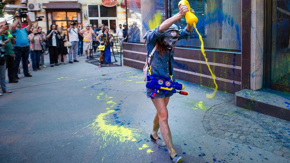 A protestor empties a bottle of coloured paint on the public office of President Gjorge Ivanov during an anti-government protest in Skopje on 31 May 2016, in a series of protests dubbed Colourful Revolution.