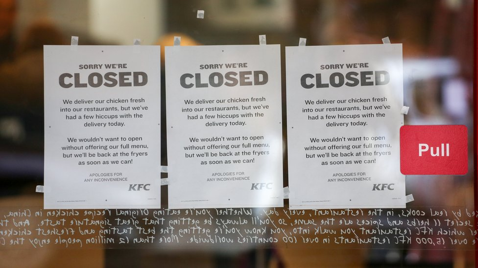 Signs in a KFC shop door which say that the store is closed due to a shortage of chicken