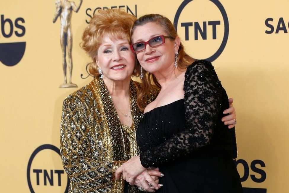 Actress Debbie Reynolds poses with her daughter actress Carrie Fisher backstage after accepting her Lifetime Achievement award at the 21st annual Screen Actors Guild Awards in Los Angeles, California January 25, 2015.