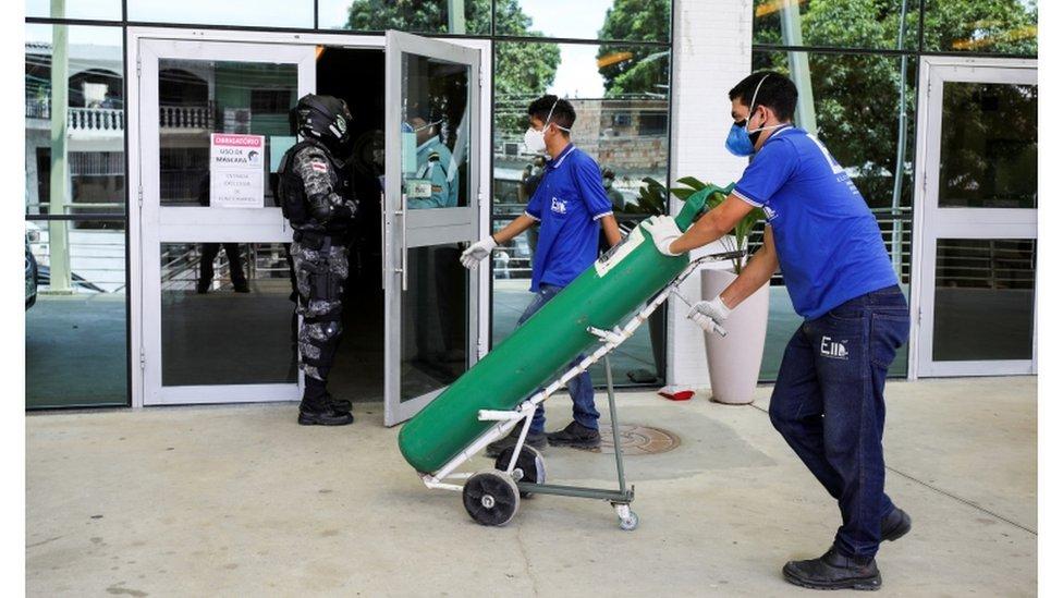 Homem leva cilindro de oxigênio para hospital em Manaus
