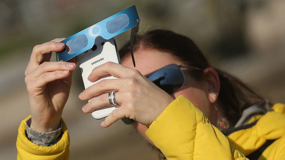 Mujer sacando foto al eclipse con su celular.