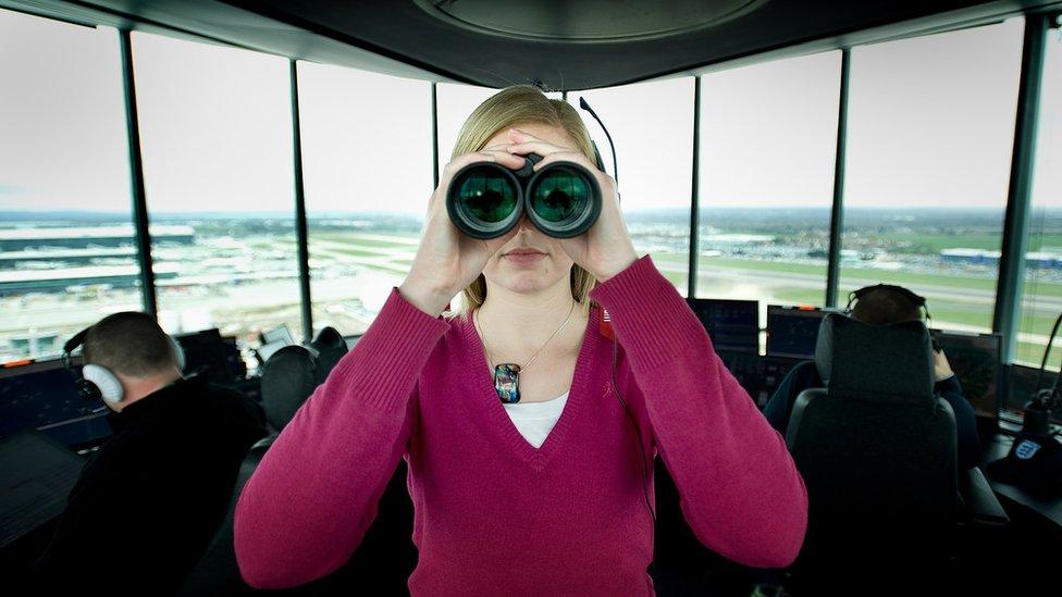 Air traffic controller holding binoculars