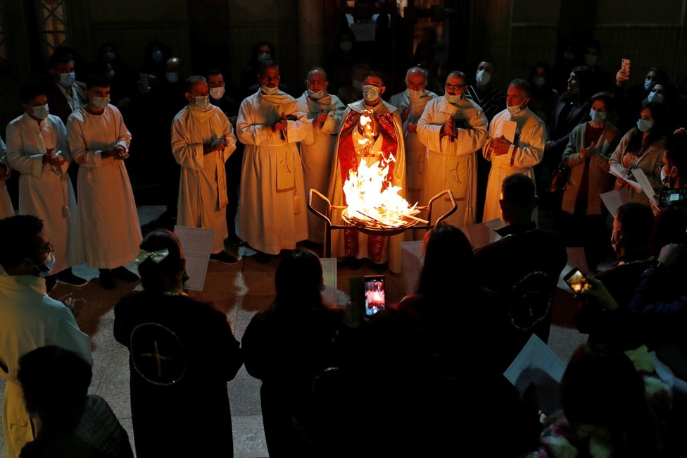 People gathered around a fire during a Mass in the Virgin Mary Church in Baghdad, Iraq. Photo: 24 December 2020