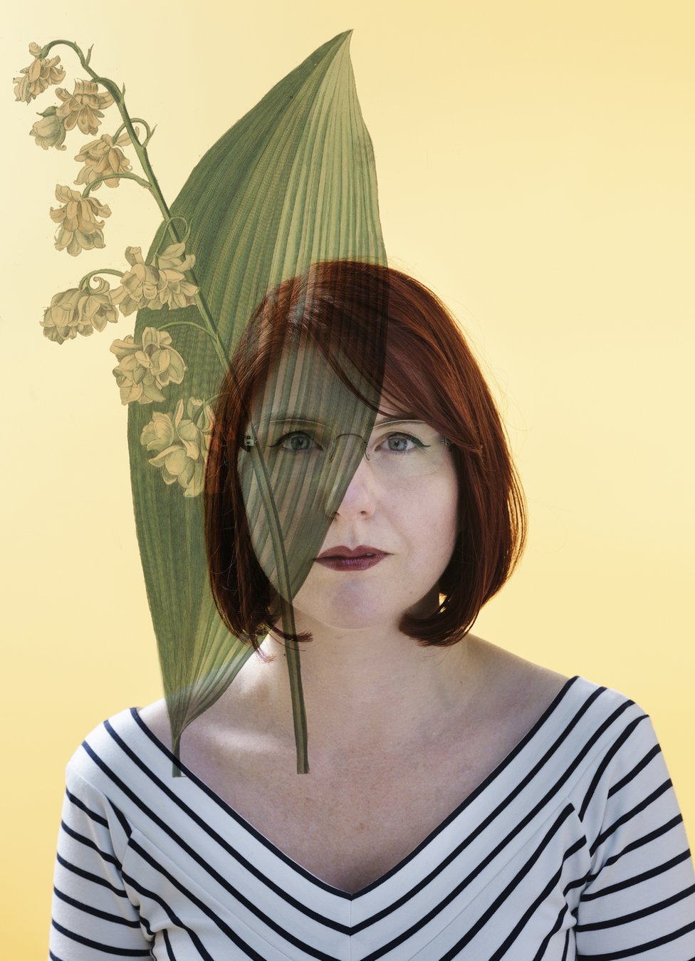 A portrait of a woman with her face partially covered by a leaf.