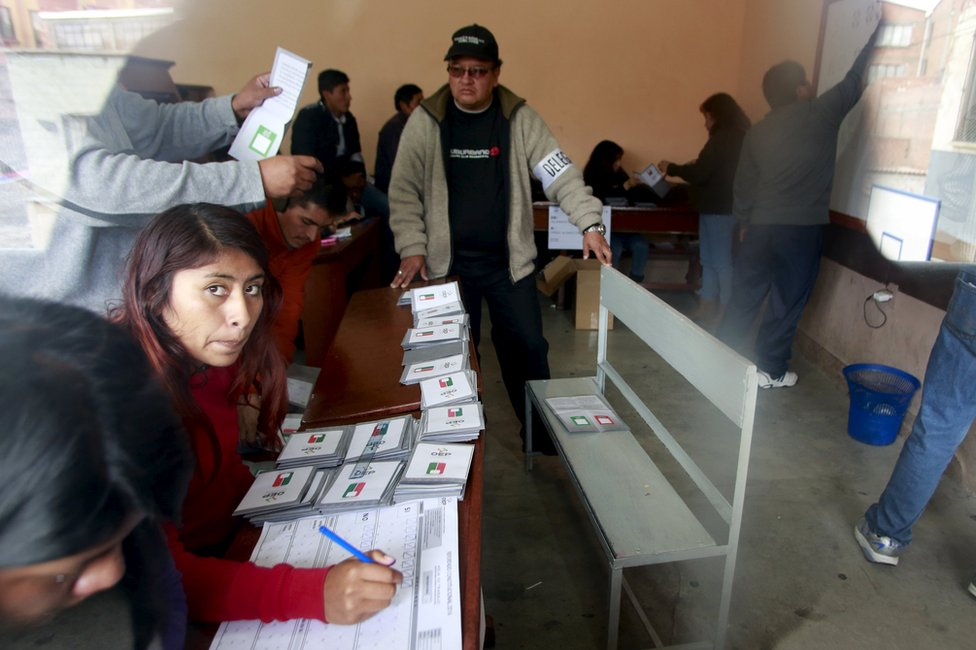 Members of the electoral polling committee count votes during a national referendum in La Paz, Bolivia, 21 February