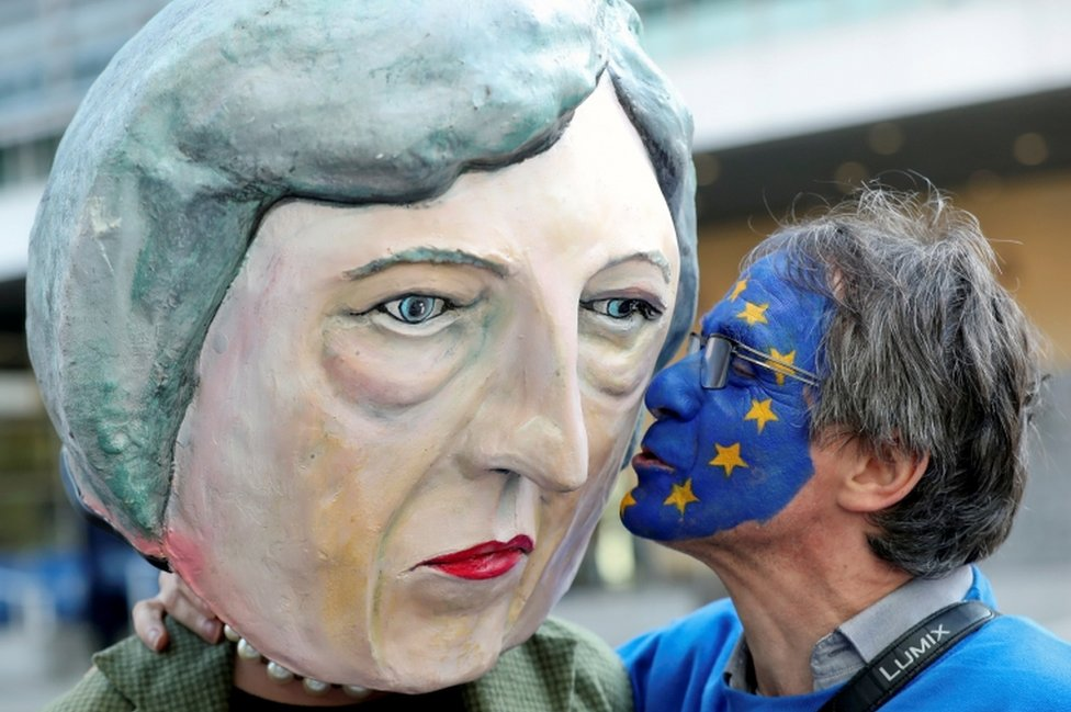 An anti-Brexit protester kisses a Theresa May head before a summit in Brussels
