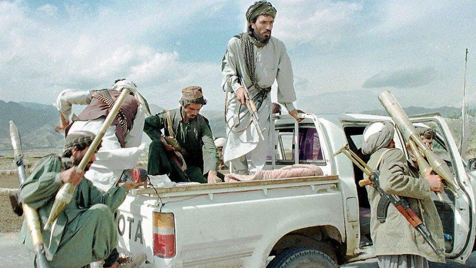 Los combatientes de la milicia talibán suben a bordo de su camioneta Toyota con lanzacohetes antitanque RPG-7 y rifles de asalto.