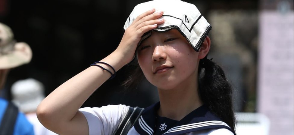 A Japanese high school student uses a handkerchief to cover her head from sunlight