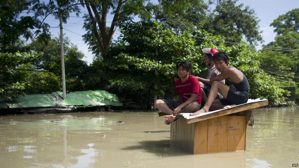 Men sit on a flooded roof in Sagaing, Myanmar (3 Aug 2015)