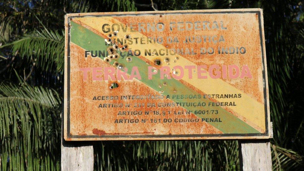 Yerlilerin yaşam alanlarının girişindeki tabelada kurşun izleri görülüyor.