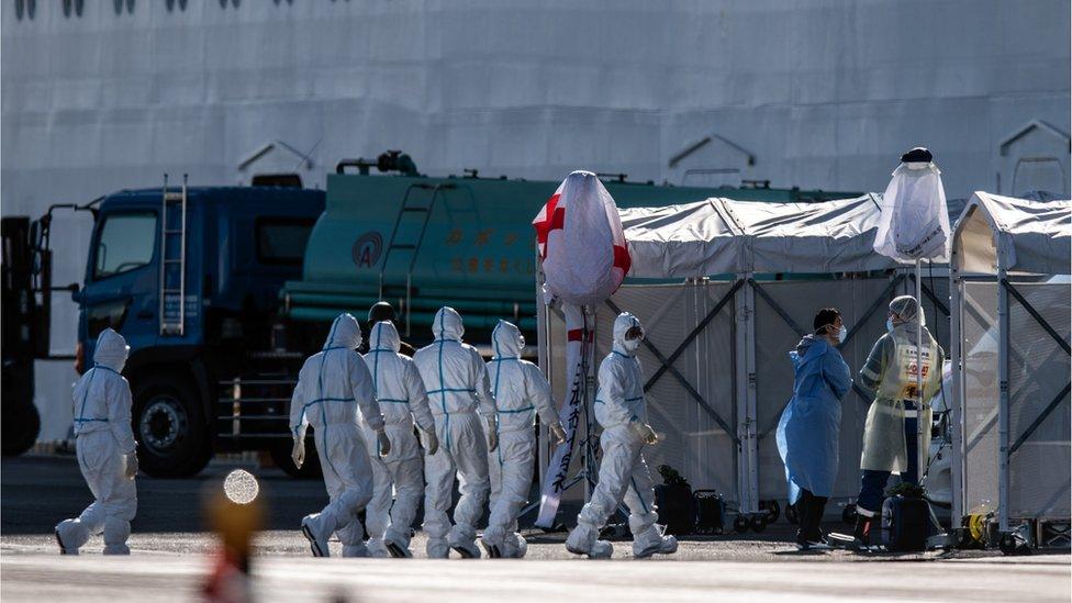 الطاقم الطبي أمام سفينة دايموند برنسيس في اليابان