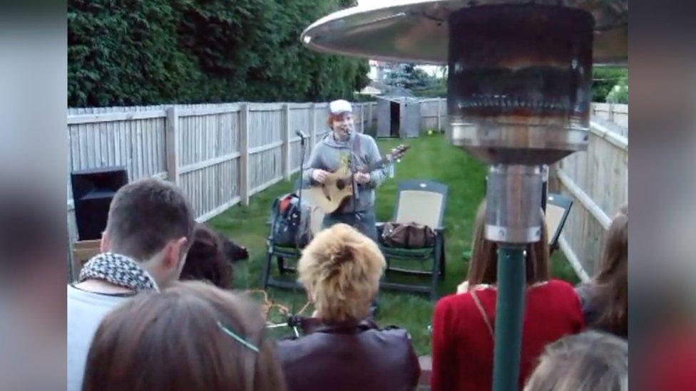 Ed Sheeran performing in a garden