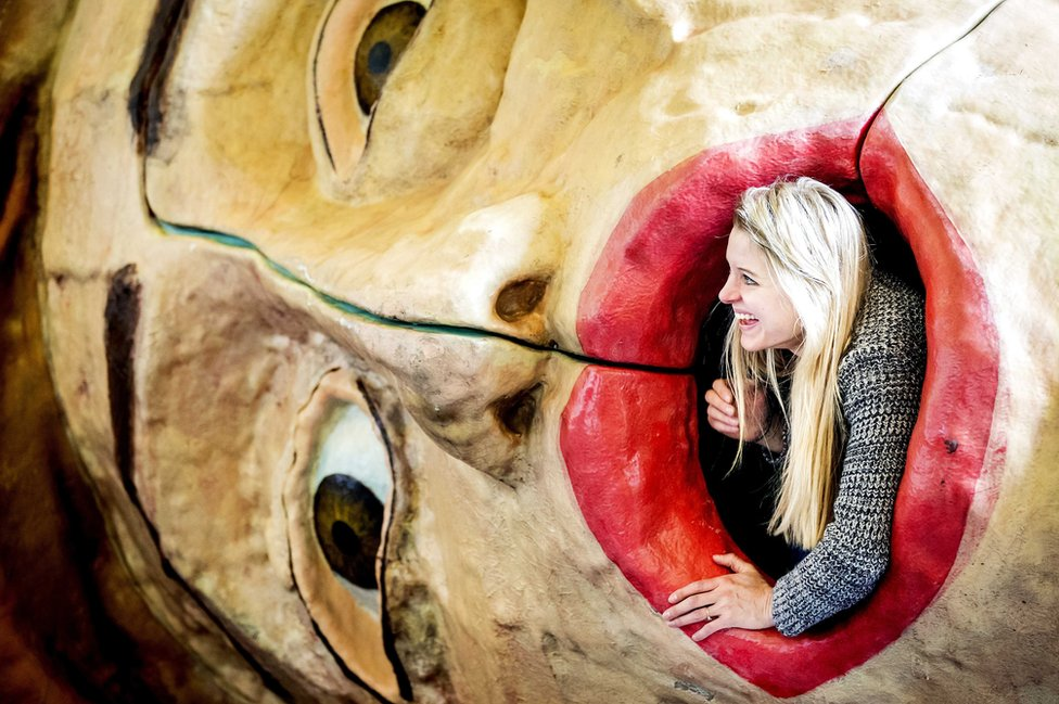 امرأة تخرج من عمل فني خلال معرض كونستراي للفن في أمستردام. ويقول القائمون على المعرض إنه الحدث الفني الأقدم من نوعه في هولندا.