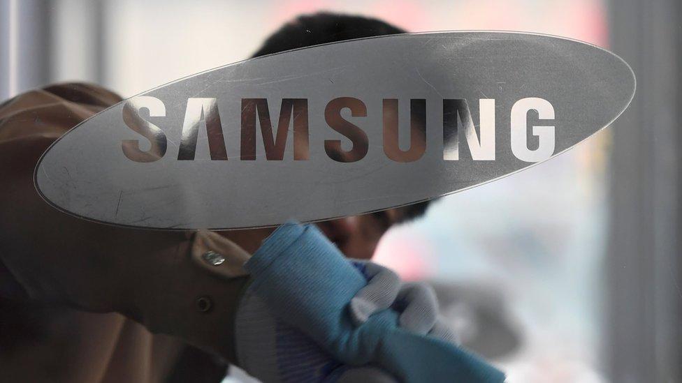 Un hombre limpiando un vidrio con el logo de Samsung.