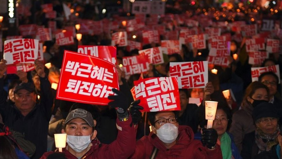"Protesters in Seoul hold banners that read: ""Step down, Park Geun-hye"""