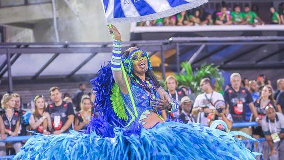 Lucinha Nobre segura bandeira enquanto desfila na Sapucaí em 2020, com fantasia azul e verde cheia de plumas