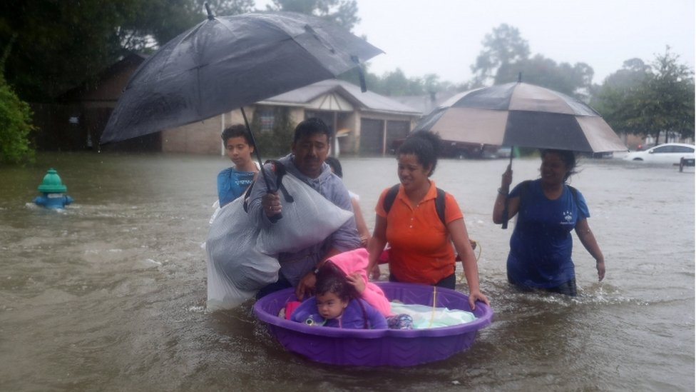 People walk down a flooded street as they evacuate their homes after the area was inundated with flooding from Hurricane Harvey on 28 August 2017 in Houston, Texas